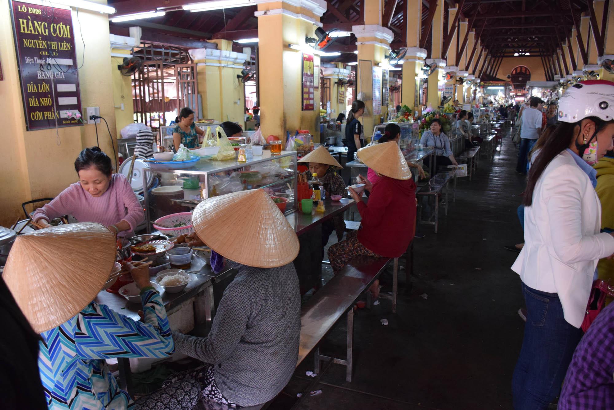 Vietnamitas almoçando no mercado em Hoi An