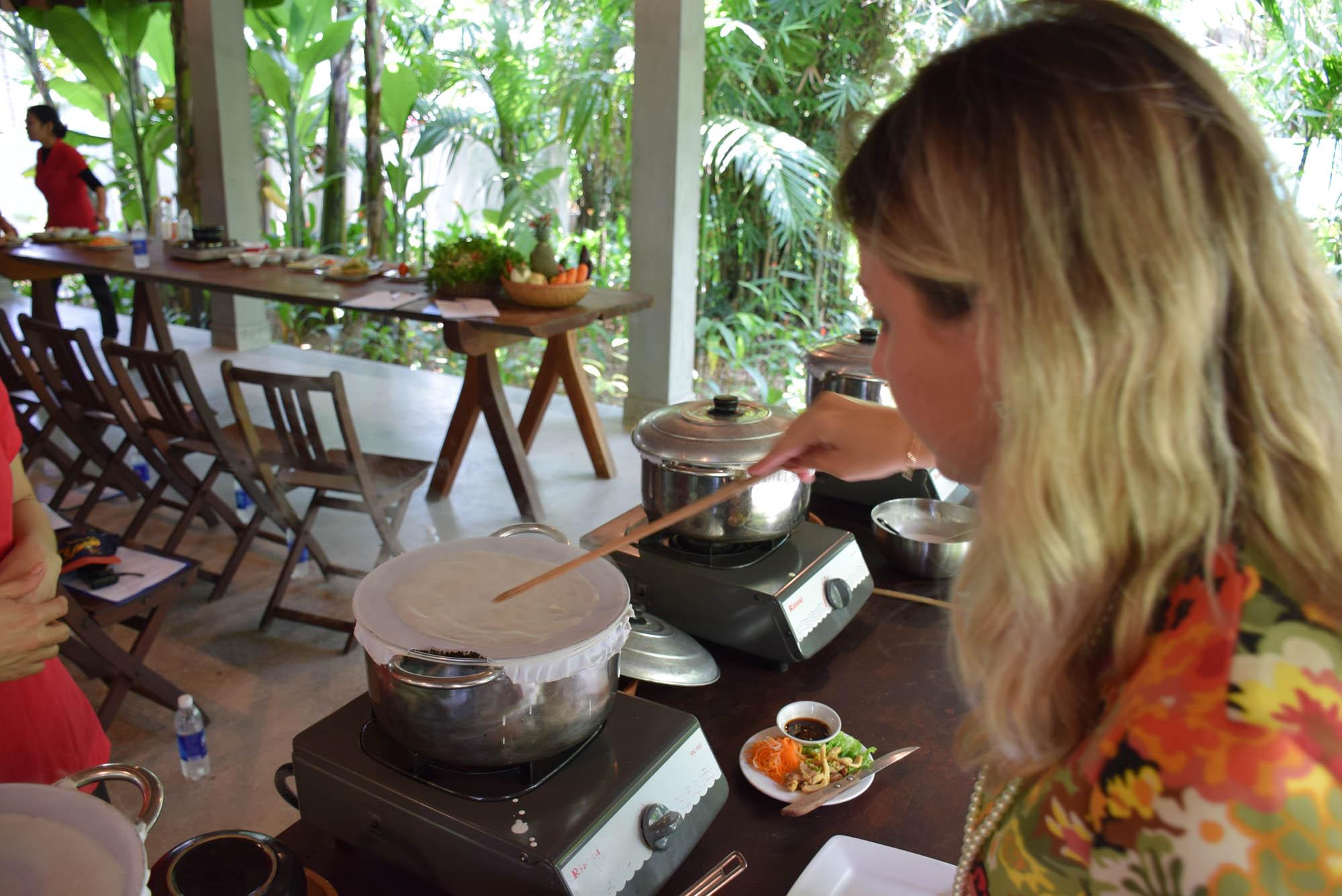 Eu fazendo papel de arroz com varinha de bambu, na aula de culinária Red Bridge em Hoi An