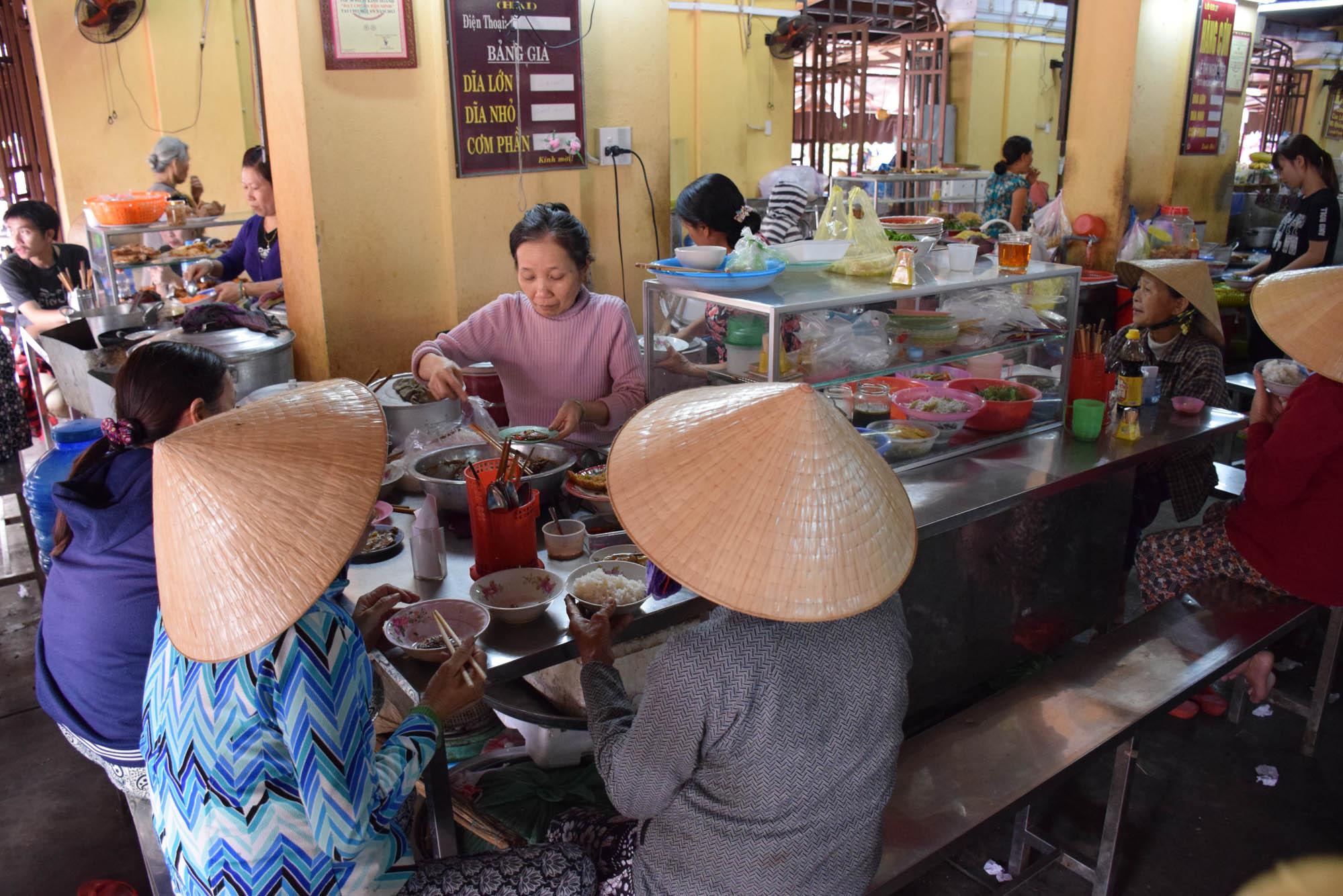 Vietnamitas almoçando no Mercado Central de Hoi An (muito fofas de chapeuzinho, né?!)