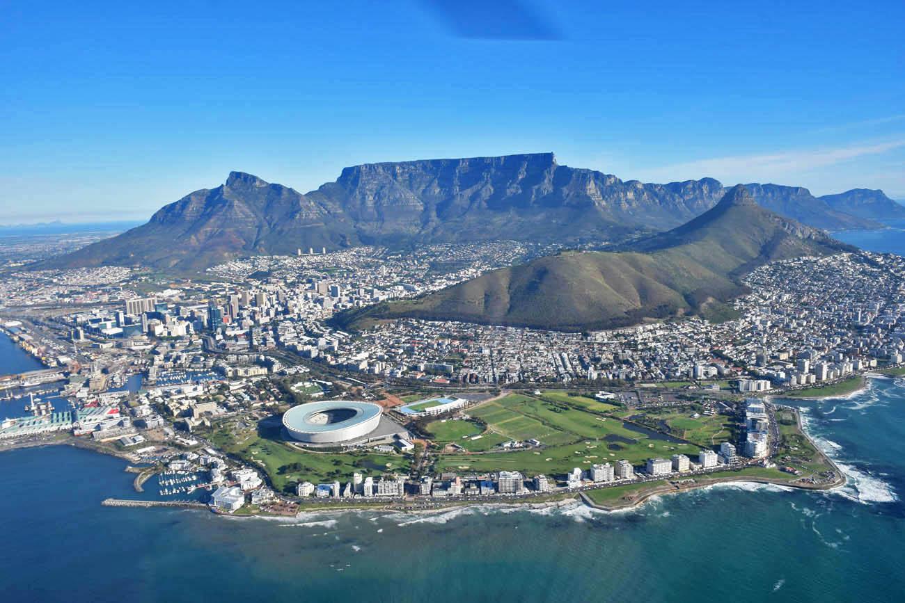 Table Mountain atrás e o estádio na frente | Sobrevoando a Cidade do Cabo de helicóptero - NAC Helicopters