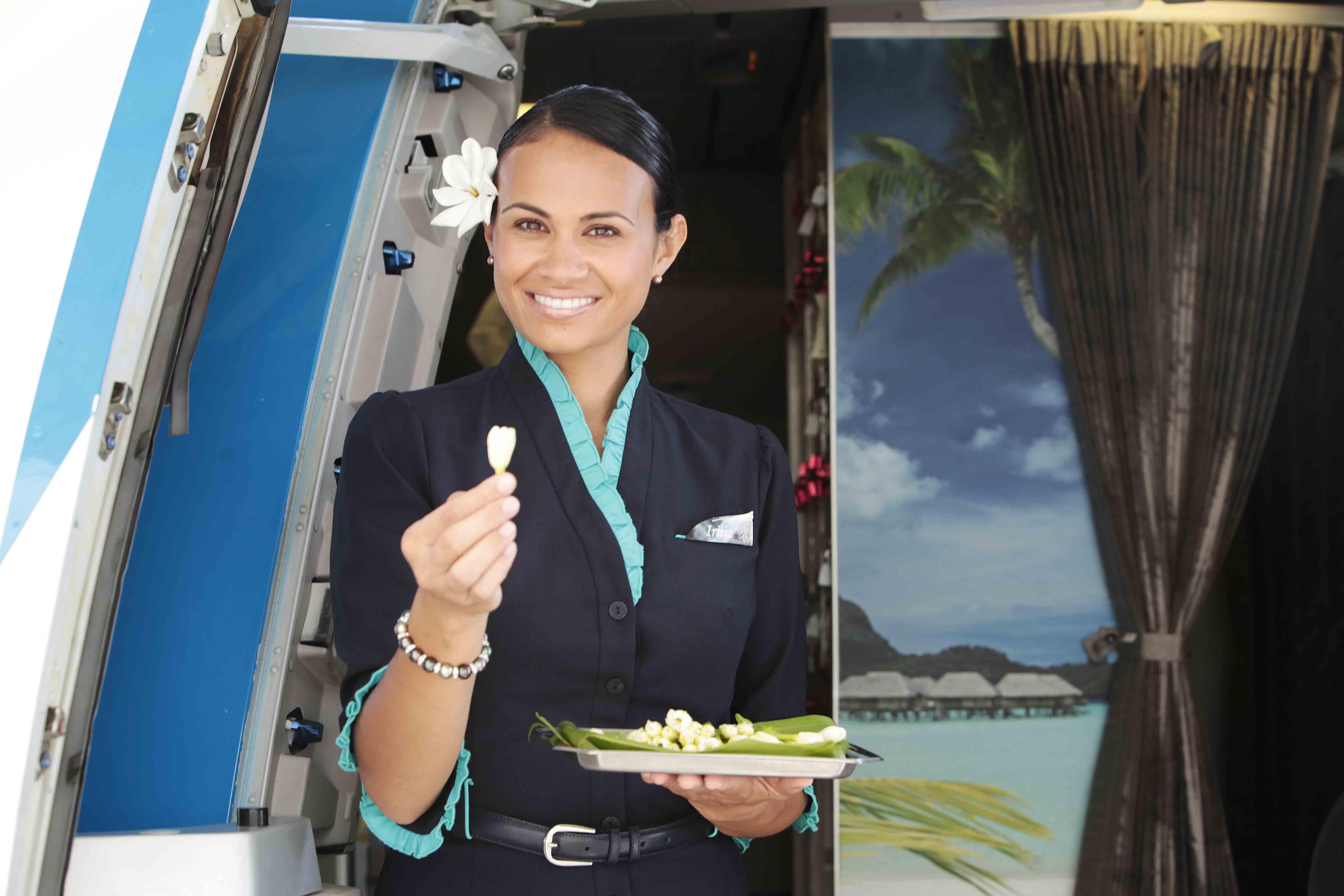 Comissária da Air Tahiti Nui oferecendo a flor símbolo do Tahiti, tiare, aos passageiros | foto: divulgação